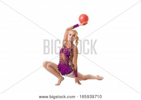 Young blonde girl in artistic embroidered violet sportsuit exercising with a red ball studio portrait