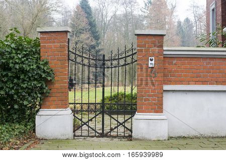Little Iron gate surrounded with ivy and stone pillars