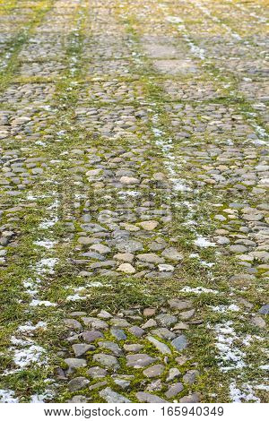Road with grass and little round stones