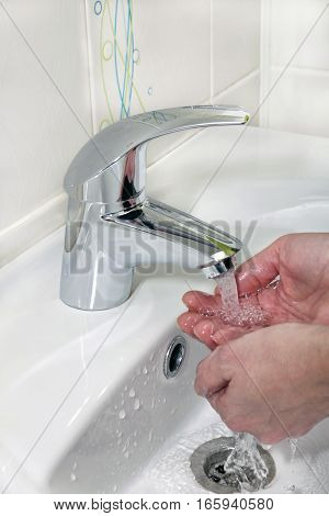 washing hands under a stream of water