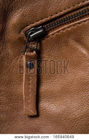 Brown textured leather jacket zippers. Leather jacket macro details. Jacket zippers and pockets