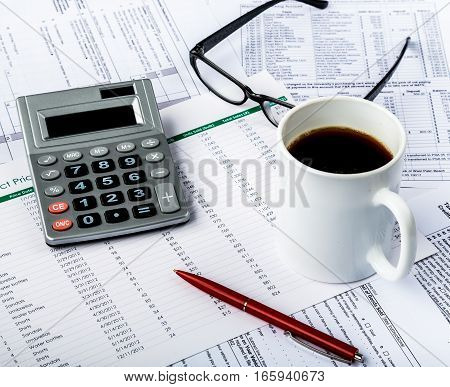 Calculator, Pen, Eyeglasses and Coffee on Financial Figures
