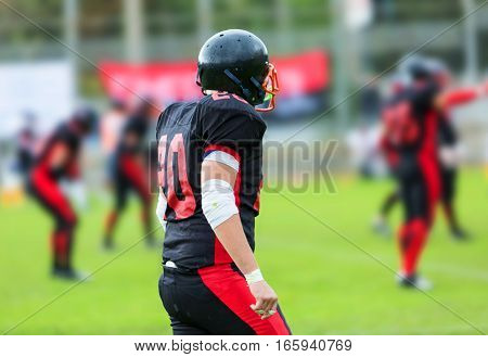 American Football Player With His Teammatess In Background Close-up