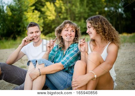 Children with their loving mother having chocolate, outdoor shot.