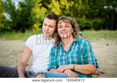 Smiling mature relaxed woman. Son leaning on his mother.