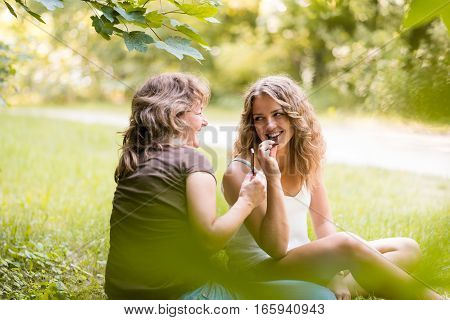 Happy teenage daughter with mother eating chocolate bar