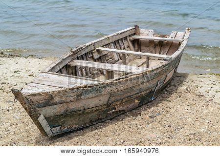 Old wooden boat forgoten on the lake beach