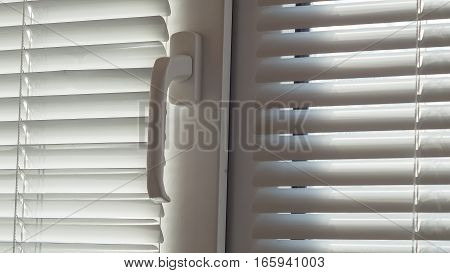 The blinds and closed window on sunny day