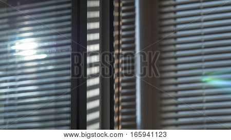 The sun is glow shining through the blinds