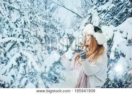 beautiful girl playing in the snow in the forest