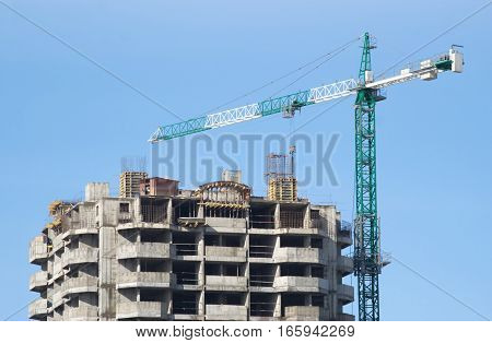 Big hoisting tower crane and top of construction building isolated on blue