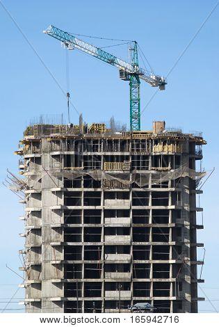 Big hoisting tower crane and construction building