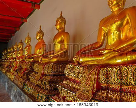 Statues of the sitting Buddha in the ancient buddhist Temple, Bangkok, Thailand. Selective focus