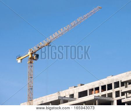 Big yellow construction tower crane on building over blue sky