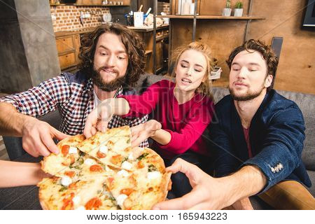 Smiling friends tasting pizza while sitting on sofa