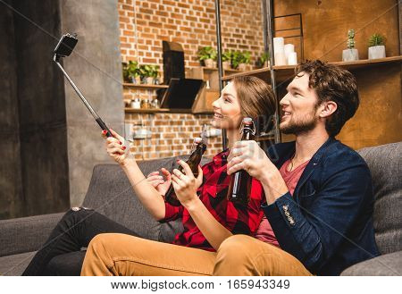 Happy young couple with beer taking selfie
