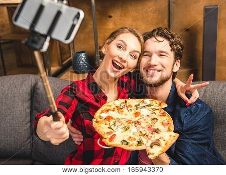 Happy young couple taking selfie with pizza