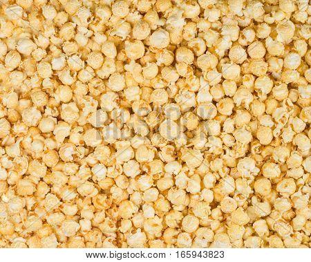 Scattered caramel popcorn texture background. Square format