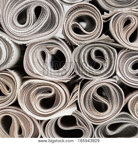 Stack of newspapers rolls paper texture background.