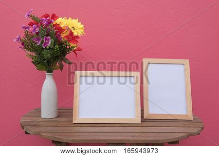 Two photo Frame on a wooden and Flowers in jar on pink background .