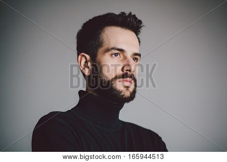 Portrait of a handsome bearded young man looking a side