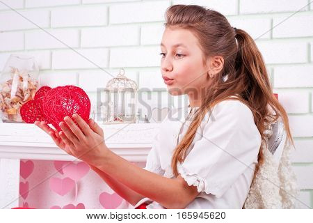 Beautiful young girl holding decorative heart and kissing it; studio portrait in valentines decor