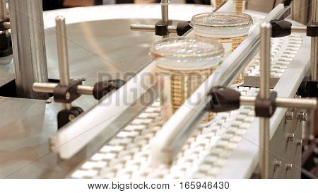 Conveyor product line for packing and marking goods and food packs. Robotics and automatic lines instead of human labor on factories and plants.