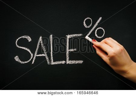woman's hand writing on the blackboard the word sale