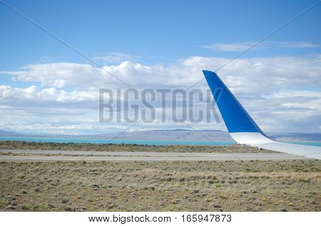 Airplane wing and view to landing strip desert and lake
