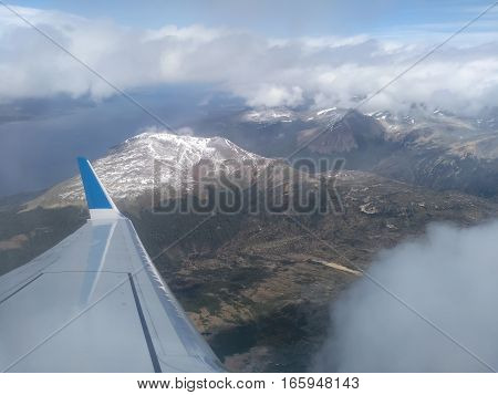 Airplane wing in the air above mountains and clouds