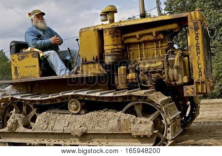 ROLLAG, MINNESOTA, Sept 1. 2016: The unknown bearded operator of a Vintage Caterpillar is  being driven at the West Central Steam Threshers Reunion in Rollag, MN attended by 1000's held annually on Labor Day weekend.