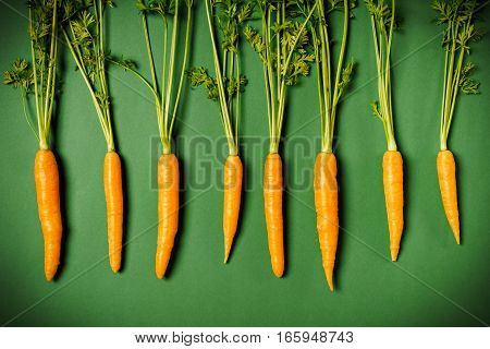 some fresh orange carrots on a green background