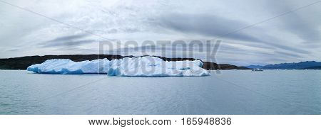 Panoramic view to iceberg and a boat