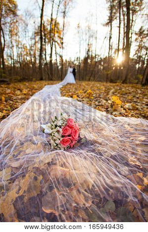 Bride and groom at sunset and bridal bouquet on a long bridal veil