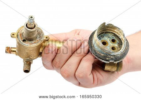 Old broken faucets for the shower in the hand isolated on a white background.