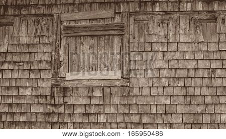 Old wooden barn wall with weathered shingles