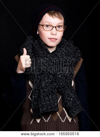 small smiling boy or cute nerd kid in glasses hat and fashionable knitted scarf on black background holds thumb up