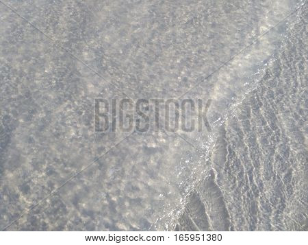 Clear sea watter above sandy bottom of the sea