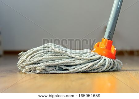 cleaning wooden floor with orange wet mop