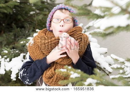 small surprised boy or cute nerd kid in glasses hat sweater and fashionable knitted scarf holds pig moneybox in winter outdoor at green fir tree with snow on natural background