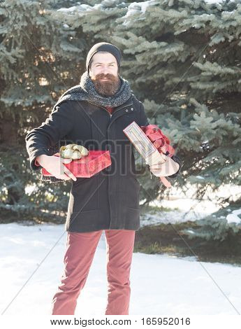 Happy bearded man handsome hipster with beard and moustache in black hat coat and scarf smiles with gift boxes as presents on sunny winter day outdoors on natural background