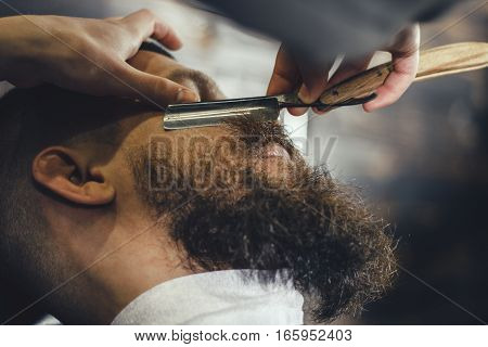 Young Bearded Man Getting Beard Haircut With A Vintage Straight Razor By Barber. Barbershop Theme