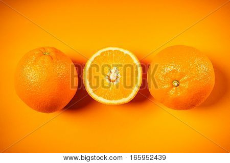 three fresh and juicy oranges on an orange background
