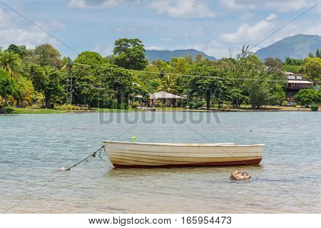 Wooden boat on the river where the Indian Ocean meets the river Tamarin Black River District Mauritius. Villas in the background.