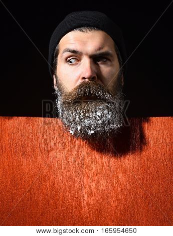 handsome bearded man or guy in winter hat with fashionable mustache on surprised face and snow in beard near red paper on black background copy space