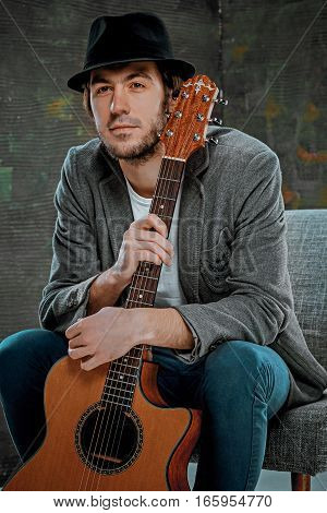 Cool guy with hat sitting with guitar on gray studio background
