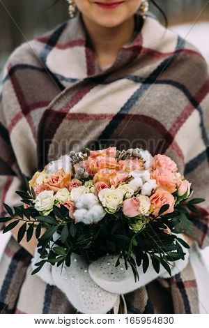 Bride holding her wedding bouquet in hands of the winter. In the hands put on the white gloves. The bouquet presentedin roses and other flowers in white and pink.