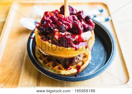 waffles and chocolate icecream with fresh berries on wooden tray