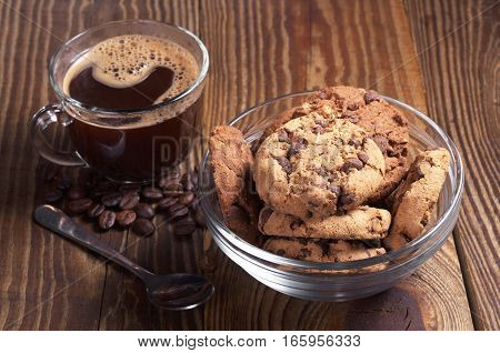 Cup of hot coffee and chocolate cookies in bowl on old wooden