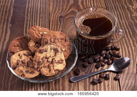Cup of hot coffee and cookies with chocolate in plate for breakfast on old wooden table